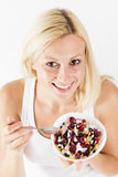 Woman eating muesli. Happy blonde woman eating muesli with fruit at breakfast Stock Image