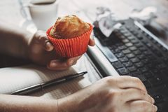 Woman eating muffin at workplace. Unhealthy snack. Unhealthy snack at work time. Woman eating muffin at workplace. High calorie, fattening junk food, weight gain royalty free stock photos