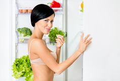Woman eating near the opened fridge Stock Images