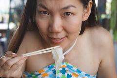 Woman eating noodles Stock Photos