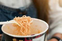 Woman eating noodles cup with a Plastic Fork royalty free stock photos