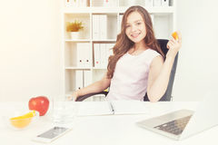 Woman eating orange and apple Royalty Free Stock Images