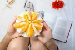 Woman eating orange fruit in bed Royalty Free Stock Image