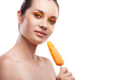 Woman eating orange ice-cream and having fun Stock Photos