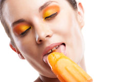 Woman eating orange ice-cream and having fun Royalty Free Stock Image
