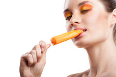 Woman eating orange ice-cream and having fun Stock Photo
