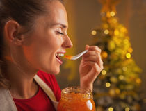 Woman eating orange jam in christmas decorated kitchen Stock Photos