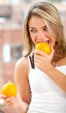 Woman eating oranges Stock Photography