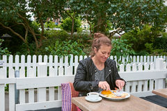 Woman eating at an outside cafe Royalty Free Stock Photos