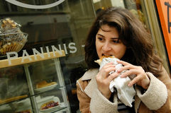 Woman eating panini. A woman eating panini at a panini shop Stock Image