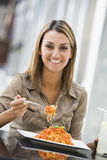 Woman eating pasta at cafe. Woman eating plate of pasta at cafe Royalty Free Stock Photos
