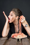Woman eating pasta at wooden table Stock Photos