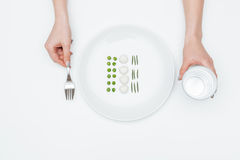 Woman eating peas, mozzarella, herbs and holding glass of water Royalty Free Stock Image