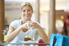 Woman Eating A Piece Of Cake At The Mall Royalty Free Stock Image