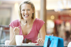 Woman Eating A Piece Of Cake At The Mall stock photos