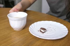 Woman is eating a piece of chocolate cake and drinks coffee. Close-up hand. royalty free stock images