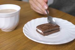 Woman is eating a piece of chocolate cake and drinks coffee. Close-up hand. royalty free stock photography