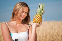 Woman eating pineapple. Summer picnic. Stock Photography