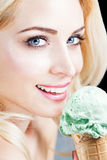 Woman Eating Pistacia Ice Cream. Attractive Blond Woman With Ice Cream, Looking At Camera Stock Photography