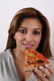 Woman eating pizza. A studio portrait of an attractive young woman with friendly smiling facial expression holding a piece of pizza in her hand royalty free stock photography