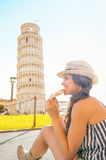 Woman eating pizza in front of tower of pisa Stock Image