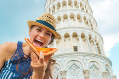 Woman eating pizza in front of tower of pisa Stock Photography