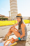 Woman eating pizza in front of tower of Pisa Stock Photo