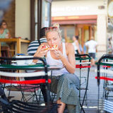 Woman eating pizza outdoor in cafeteria. Stock Image