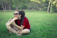 Woman eating pizza. In the park Stock Images