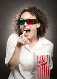 Woman eating popcorn Stock Images