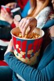 Woman eating popcorn in cinema Stock Image