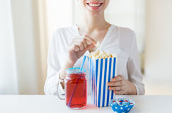 Woman eating popcorn with drink in glass mason jar Stock Photos