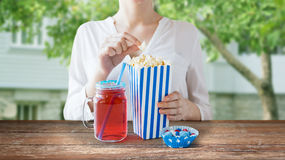 Woman eating popcorn with drink in glass mason jar Stock Image