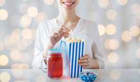 Woman eating popcorn with drink in glass mason jar Royalty Free Stock Photography