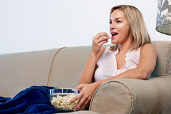 Woman eating popcorn Stock Photos