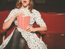 Woman eating popcorn and watching movie Royalty Free Stock Image