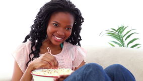 Woman eating popcorn while watching TV stock footage
