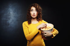 Woman eating popcorn while watching watching movie at road show. Beautiful young woman eating popcorn while watching fascinating movie and being so into plot Stock Photo