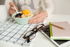 Woman eating porridge and fruits, notepad tablet and glasses on Royalty Free Stock Image