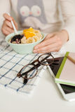 Woman eating porridge and fruits, notepad tablet and glasses on Royalty Free Stock Photos