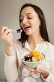 Woman eating porridge with fruits using spoon Stock Photos