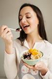 Woman eating porridge with fruits using spoon Stock Photos