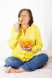 Woman eating potato chips Stock Photography