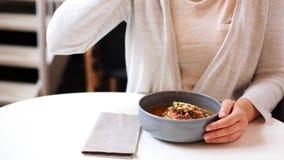 Woman eating pumpkin cream soup at restaurant stock video