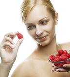 Woman eating a raspberry. Isolated over white. Happy woman eating a raspberry. Isolated over white Royalty Free Stock Image