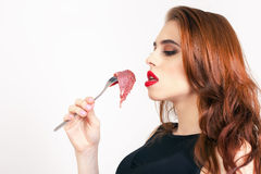 Woman eating raw meat Stock Photo