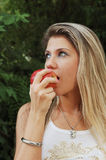 Woman eating red apple Stock Images