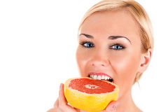 Woman eating a red grapefruit Royalty Free Stock Image
