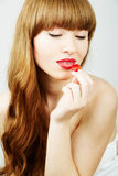 Woman eating a red jelly Royalty Free Stock Photos