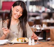 Woman eating at a restaurant Stock Images